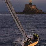 A yacht heading toward a rock with a light on