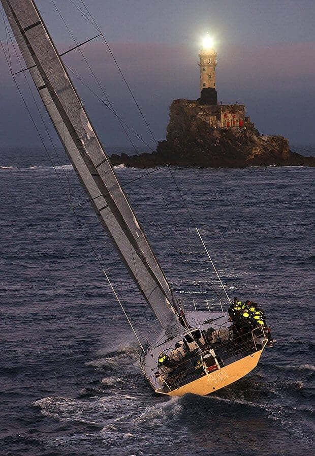 A yacht heading toward a rock with a light on