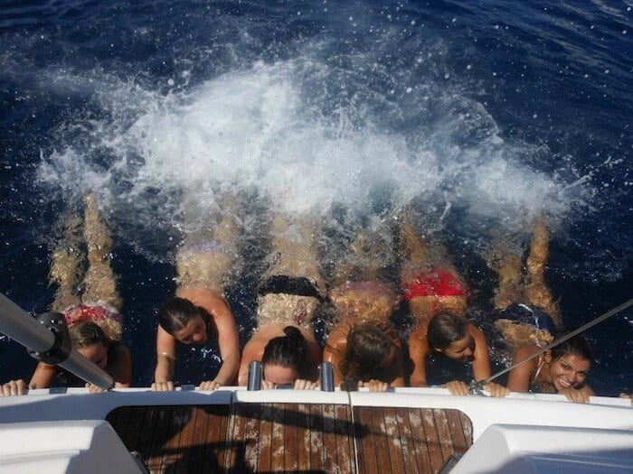 6 girls in the sea propelling a large yacht