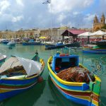 view of boats in a harbour in a small town on a malta yacht charter