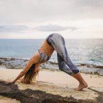 girl doing yoga on a beach