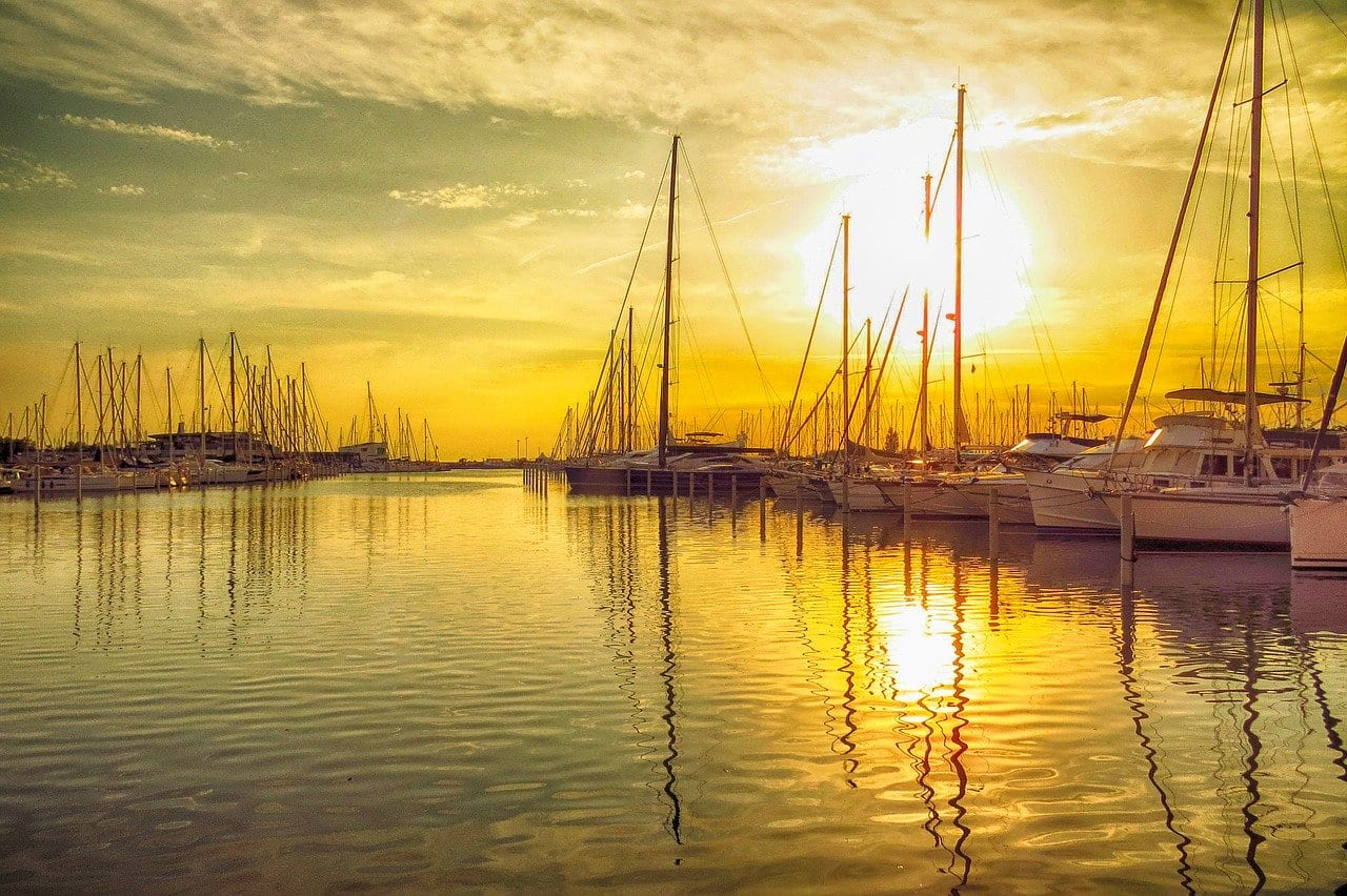 sunset in a marina when booking a sailboat charter