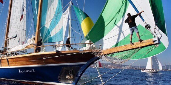 Man on the bow of a large sailing yacht with yachts in the back ground.