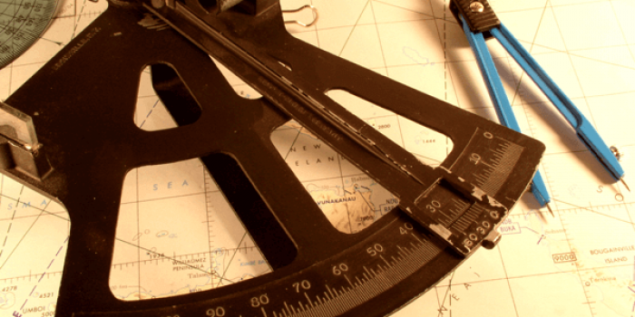 A sextant and dividers on a chart.