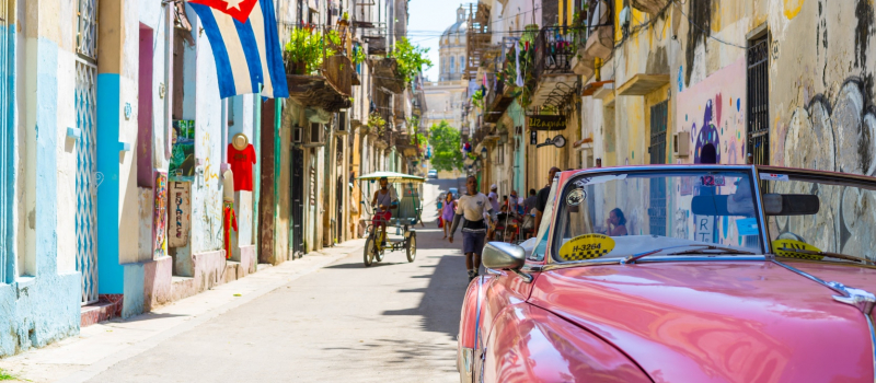 pink car and old houses in Cuba