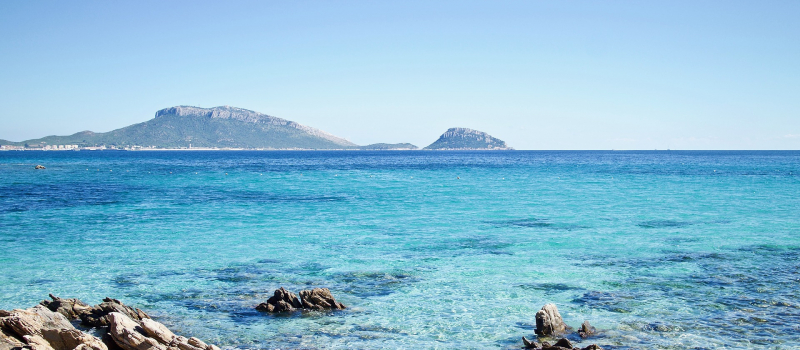 the ocean with mountains behind on a Sardinia sailing itinerary