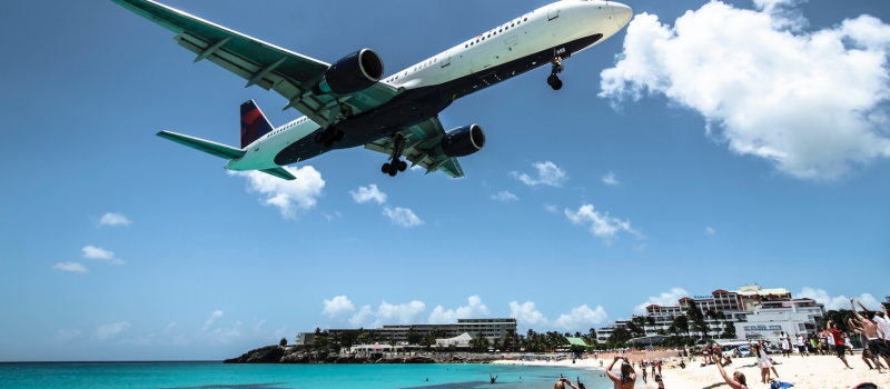 plane over a beach on a st Martin sailing itinerary